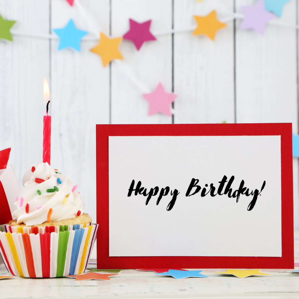 happy birthday sign with a cupcake and candle and decorations