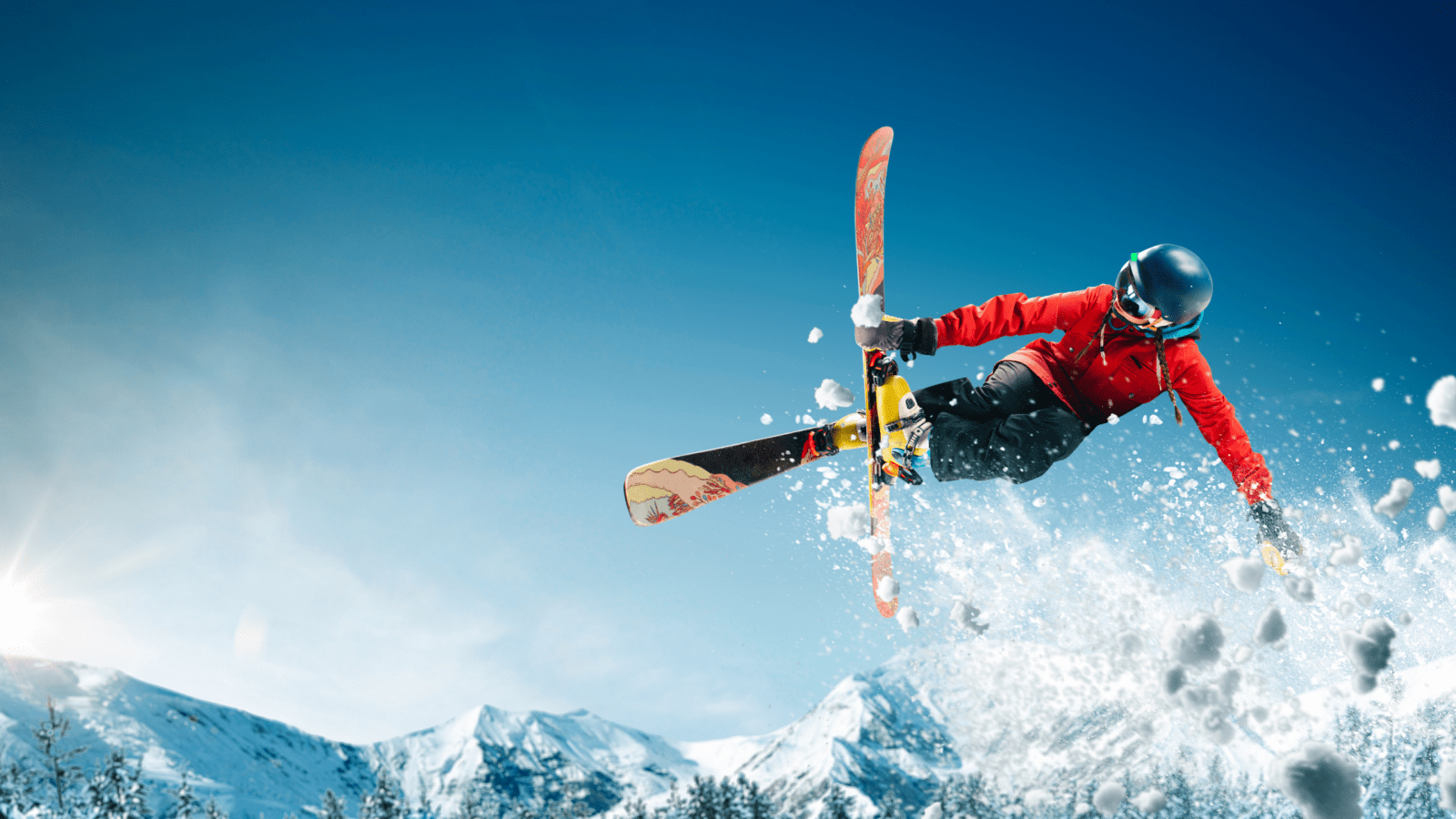 person skiing doing a trick off of a jump with mountains in the background