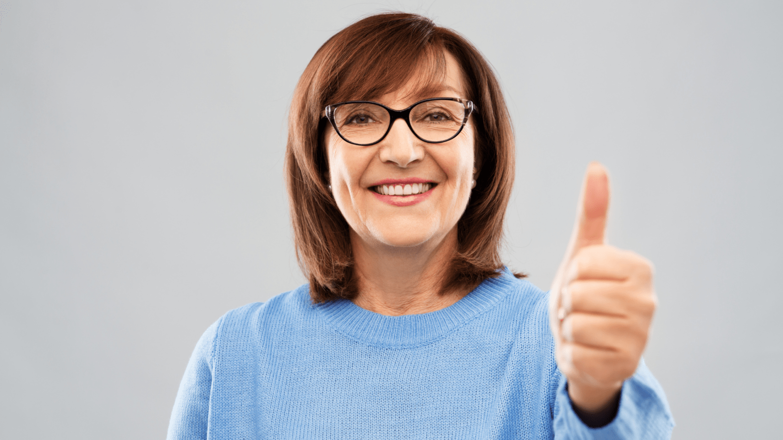 a woman with glasses giving the thumbs up gesture