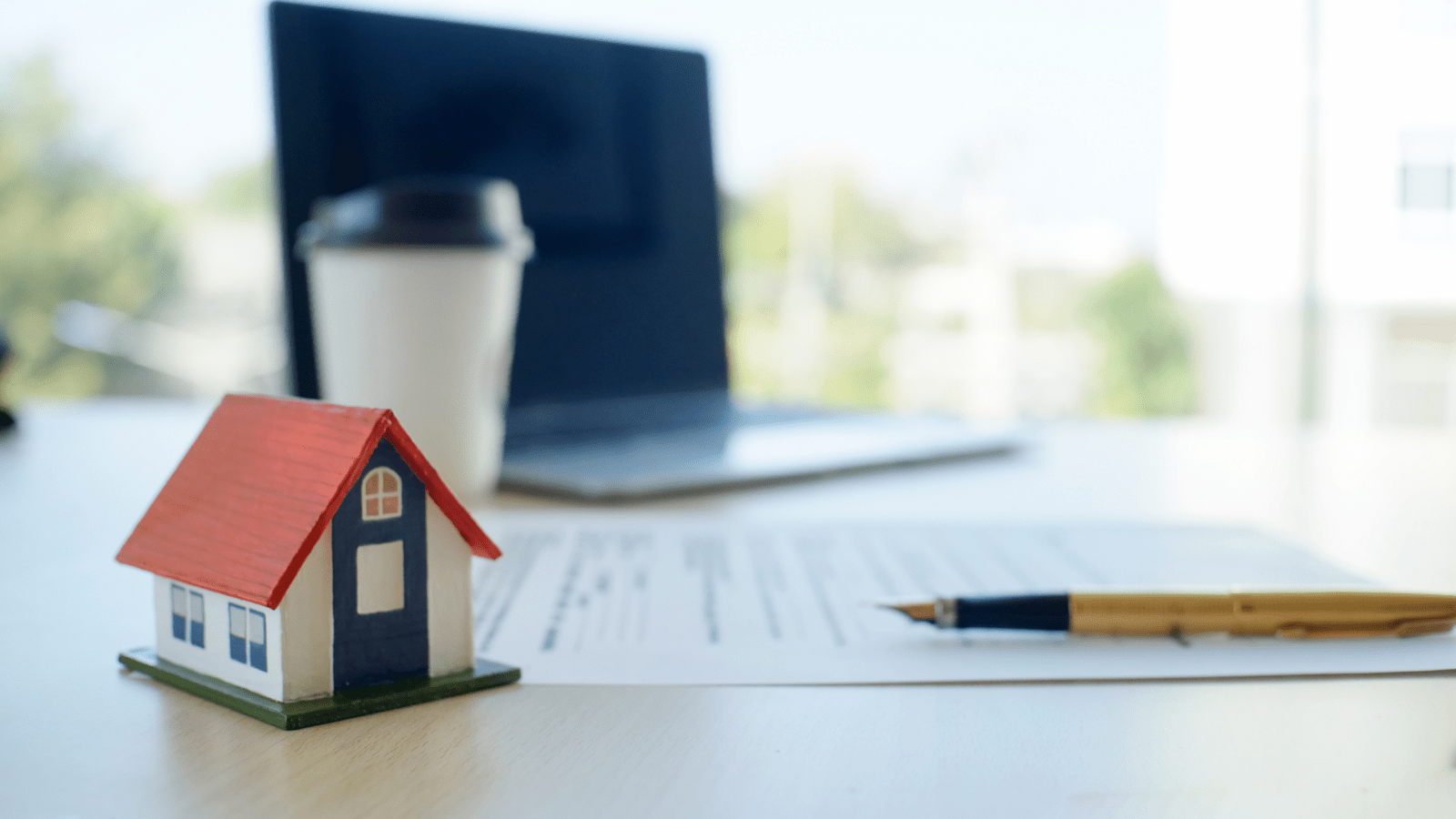 a work space with a laptop, coffee cup, pencil and paper, and miniature house