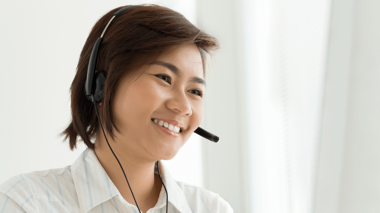woman smiling while wearing a headset with a microphone