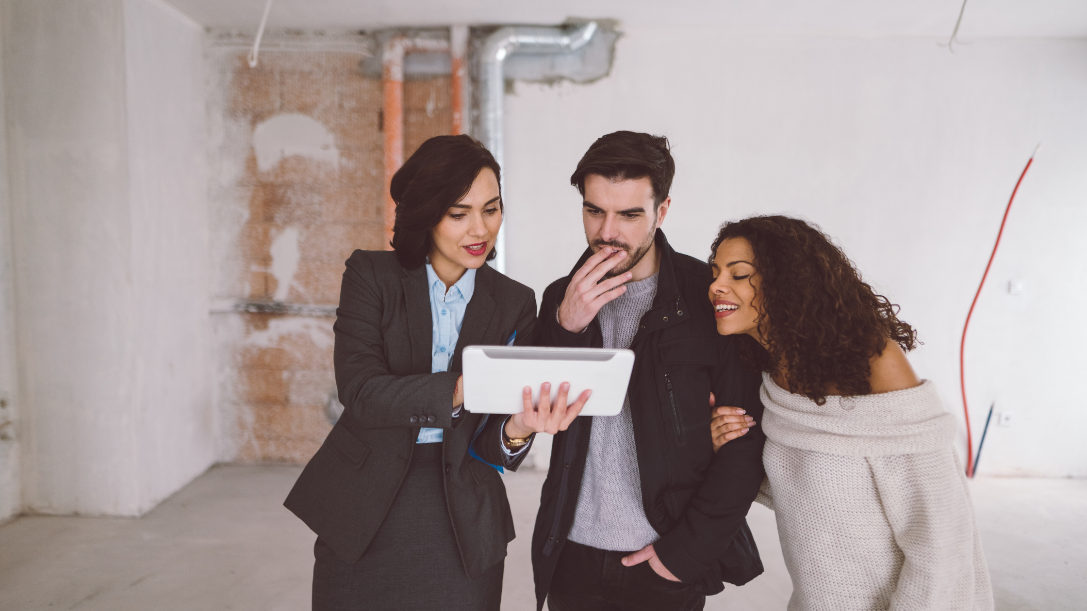 three people gathered around a tablet discussing strategy