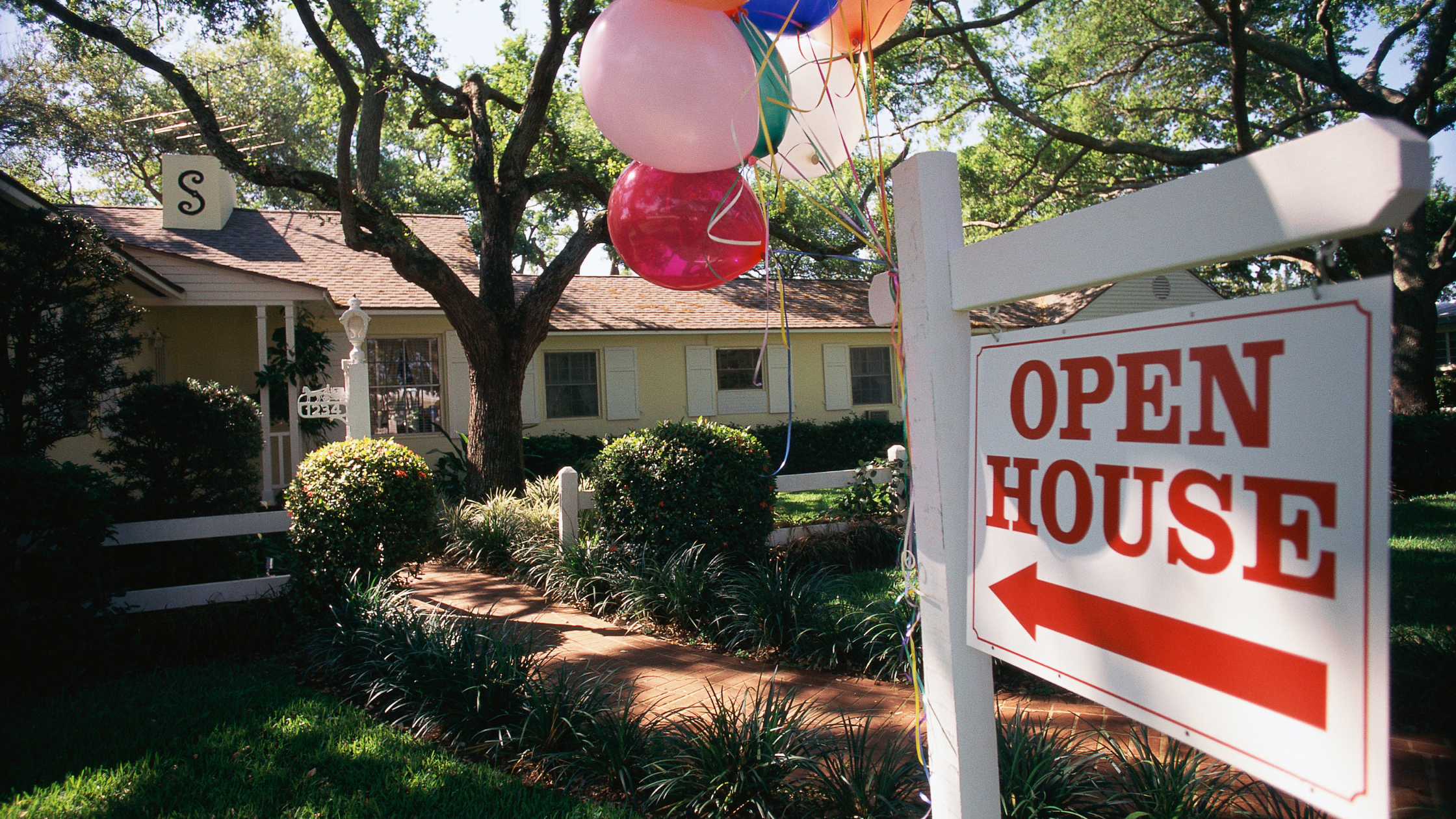 real estate sign advertising an open house with pink and red balloons